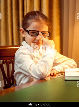 Young girl in eyeglasses sitting behind desk - Stock Photo