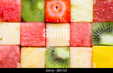 Background texture of diced tropical summer fruit cut in cubes and arranged in rows for a seamless pattern with - Stock Photo