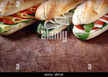 Trio of tasty vegetarian baguettes with assorted cheese fillings with basil, rocket, tomato and lettuce on crusty - Stock Photo