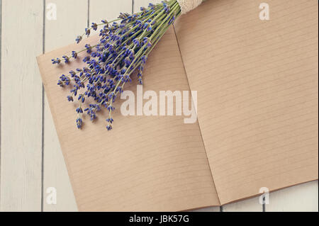 Open diary notes on the wooden table and flowers forest Lavander - Stock Photo