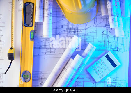 Rolls with building projects, equipment of architect: crash helmet and spirit level on wooden table. - Stock Photo