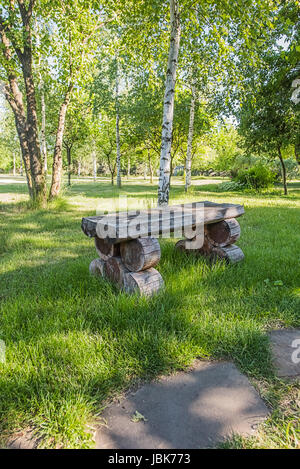 Old handmade wooden bench standing on lawn near white birch in the park or garden, from the left of sandstone footpath. - Stock Photo
