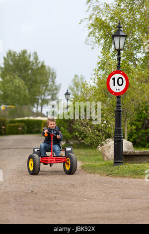 Boy driving pedal go cart next to 10 MPH speed limit sign. Trademarks have been removed. - Stock Photo