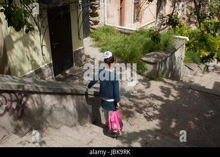 Little girl with a school backpack goes down the stairs - Stock Photo