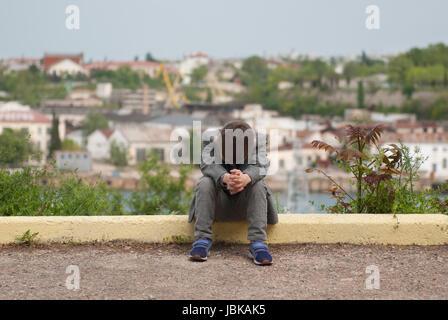 Sad little boy sitting on the curb - Stock Photo