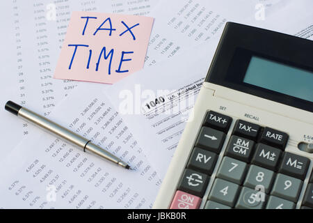 Tax Time written on pink sticker note with on U.S. tax form - Stock Photo