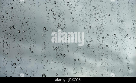 Closeup of raindrops on glass with rain clouds in the background - Stock Photo