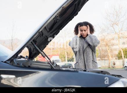 Desperate woman after checking her car broken engine - Stock Photo