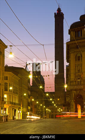 BOLOGNA, ITALY - MARCH 15, 2014: Torre Asinelli and Torre Garisenda towers at dusk from Via Rizolli. - Stock Photo