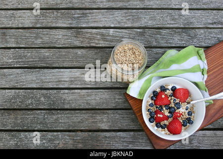 Fresh homemade healthy breakfast bowl. Granola in white bowl with greek yogurt and berries on wooden background, - Stock Photo