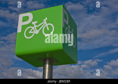 Green parking bicycle pole sign iver blue cloudy sky background - Stock Photo