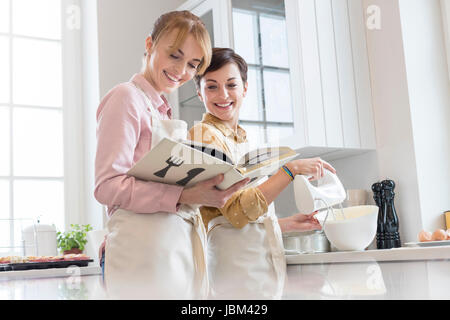 Female caterers with cookbook baking in kitchen, using electric hand mixer - Stock Photo