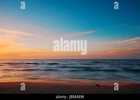Beautiful dusk at Baltic sea beach. Waves blurred by long exposure. Gdansk Bay, Pomerania, Poland. - Stock Photo
