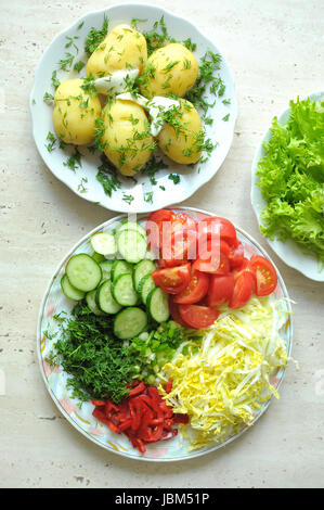 Fresh organic vegetables and boiled new potatoes on three plates on the wooden table. Top view, flat lay. - Stock Photo