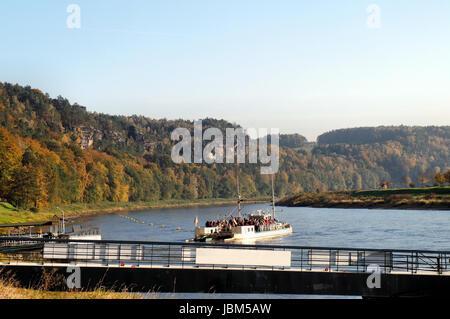 Die Elbe im deutschen Teil des Elbsandsteingebirges; steile Felsen und bunte Laubwälder; auf dem Fluss eine Fähre - Stock Photo