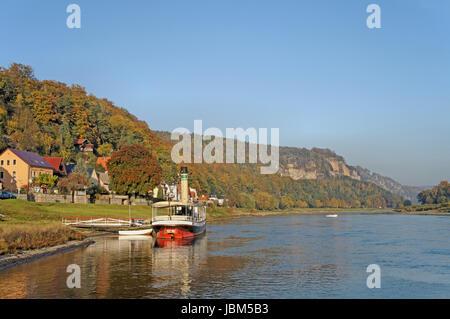 Die Elbe im deutschen Teil des Elbsandsteingebirges; steile Felsen und bunte Laubwälder; am Ufer ein kleiner Dampfer - Stock Photo
