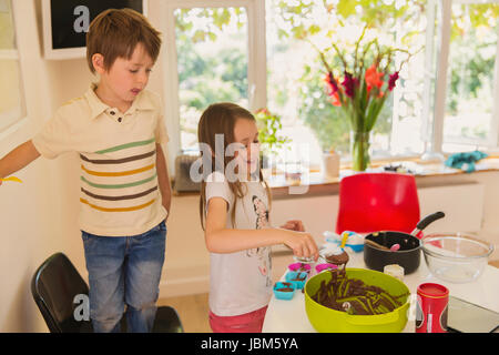 Boy and girl brother and sister making chocolate cupcakes in kitchen - Stock Photo