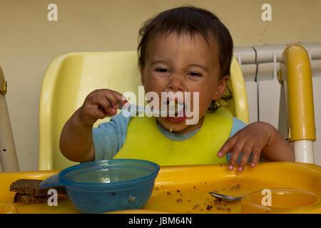 Little boy spoon eat soup - Stock Photo