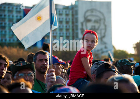 Young Cuban girl rides on man's shoulder at May Day parade  in Havana, Cuba's Revolutionary Square.  A figure of - Stock Photo