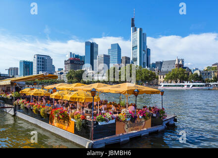 Bootshaus floating restaurant on the banks of the River Main with the skyline of the financial district behind, - Stock Photo