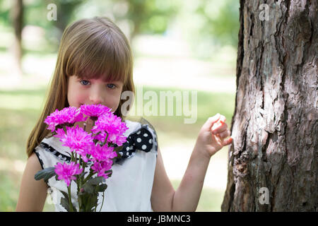 Cute little girl holding a bouquet of flowers in hand, enjoy nature and beautiful day - Stock Photo