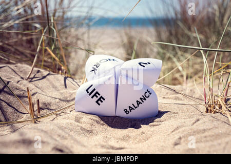Origami fortune teller on vacation at the beach concept for work life balance choices - Stock Photo