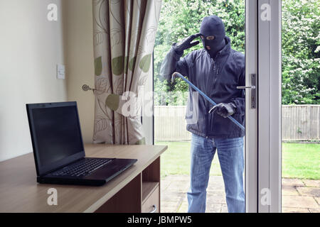 Thief breaking into a house via a patio doors window with a crowbar to steal a laptop computer from an office desk - Stock Photo