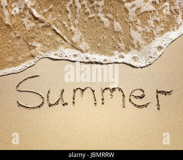 Summer written in the golden sand by the sea waves - Stock Photo