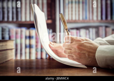 Businessman reading documents with magnifying glass concept for analyzing a finance agreement or legal contract - Stock Photo