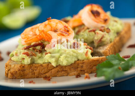 Wholegrain toast bread slices with guacamole, fried shrimp and fried bacon pieces served on plate on blue wood (Selective - Stock Photo