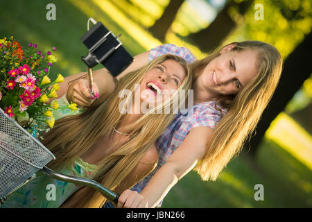 Two beautiful females taking photo of themselves with smartphone by using selfie stick in nature. Fun, youth and - Stock Photo