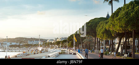 CANNES, FRANCE - SEPT 15, 2013: People walking at embankment of Cannes at sunset. 67th Festival de Cannes: from 14 to 25 May 2014