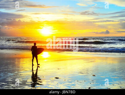 Surfer walking with surfboard on the ocean beach at sunset. Bali island, Indonesia - Stock Photo