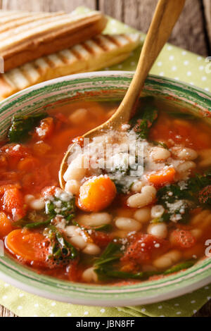Fresh hot bean soup with tomatoes, spinach, carrots and parmesan close-up in a plate. Vertical - Stock Photo