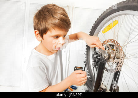 Close-up portrait of Caucasian boy repairing his bicycle, drawing up a bolt tight with spanner at garage - Stock Photo