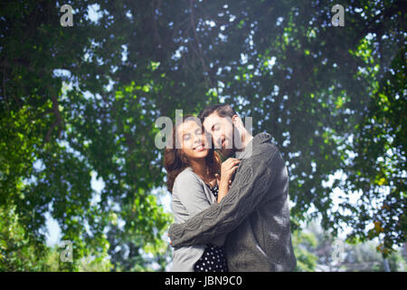Image of affectionate young man tenderly embracing his date outdoors - Stock Photo