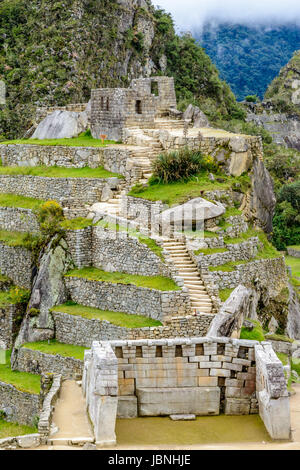Sacred plaza and the hill with intiwatana observatory rock - Stock Photo
