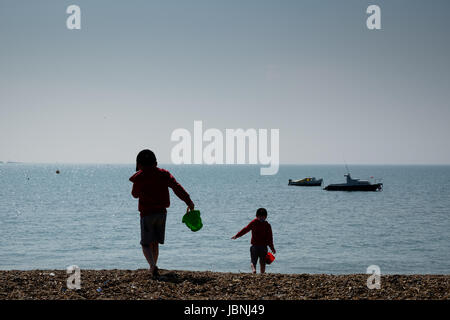twin children bucket and spades at the beach silhouette - Stock Photo