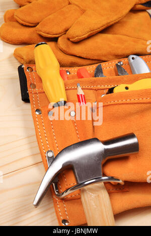 Hammer, pliers, red pencil, work gloves and other tools isolated on a wooden background - Stock Photo