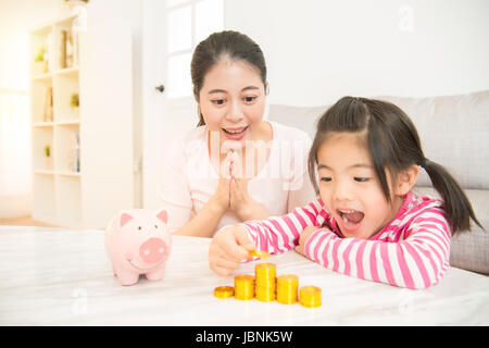 little asian chinese girl kids excited to see how much money she has deposit in her piggy bank with her mother in - Stock Photo
