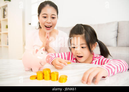 Mother teaching daughter putting coins into piggy bank. Family budget and savings concept for the future in the - Stock Photo