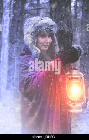 Woman with lantern in winter forest - Stock Photo