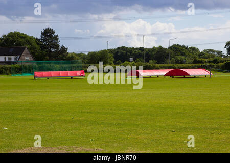 The village cricket ground in Titchfield Common in Hampshire with covers in place in readiness for the weekend match - Stock Photo
