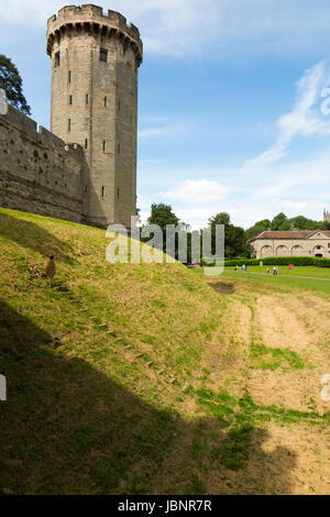 Guy's tower and rising above the ramparts and moat / grass covered dry moat of Warwick castle in Warwickshire, UK. - Stock Photo