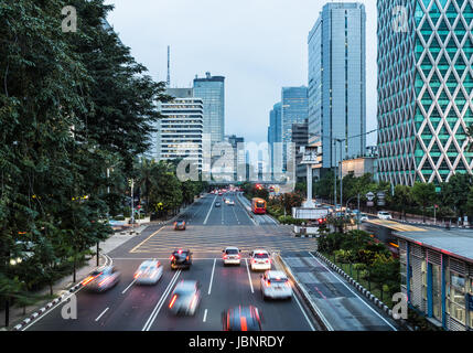 Traffic, captured with blurred motion, rush along the Thamrin avenue in the heart of Jakarta downtown district in - Stock Photo