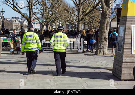 LONDON, UK - APRIL 22, 2017: London police walking on the sidewalk in the district of Westminster . - Stock Photo