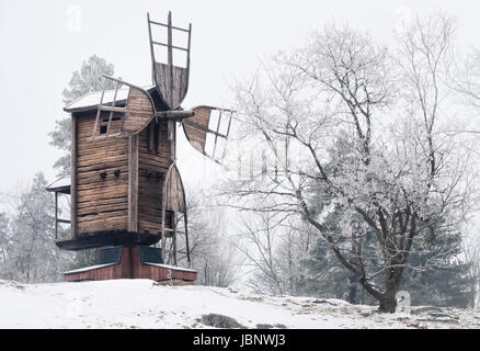 Winter landscape with old and abandoned windmill at daytime in Finland - Stock Photo