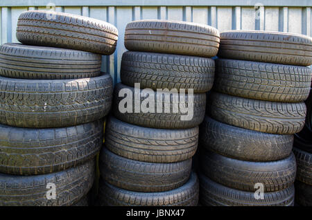 three stacks of used old tires in front of a container - Stock Photo