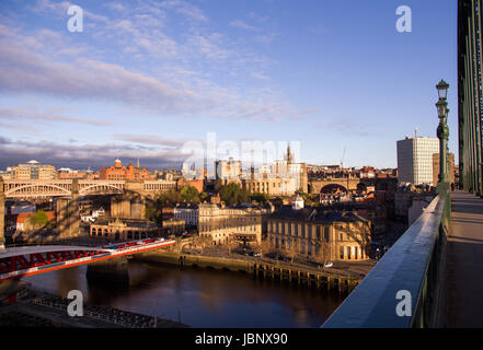 Newcastle Upon Tyne's Quayside and Grainger Town areas coloured golden at sunrise, with shadow of the iconic Tyne - Stock Photo