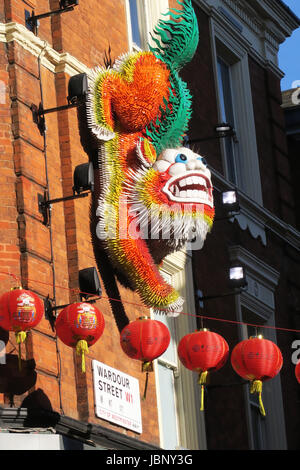 Chinese dragon hanging from wall in Wardour Street London England - Stock Photo